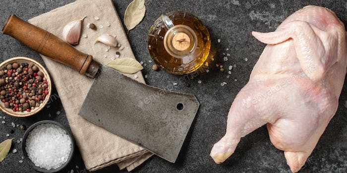 Fresh chicken, vintage butcher cleaver and spices for cooking on kitchen table