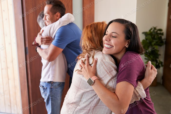 Couple Greeting Senior Parents At Front Door As They Come To Visit