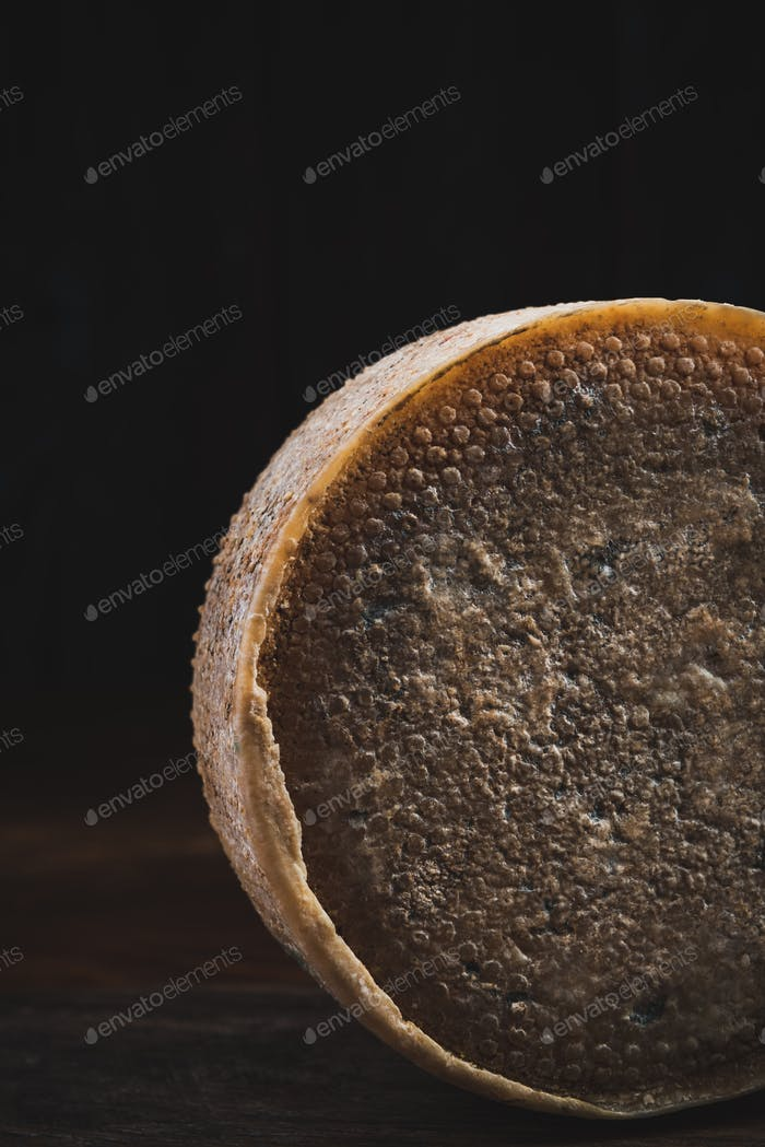 Whole Cheese Wheel on Wooden Board