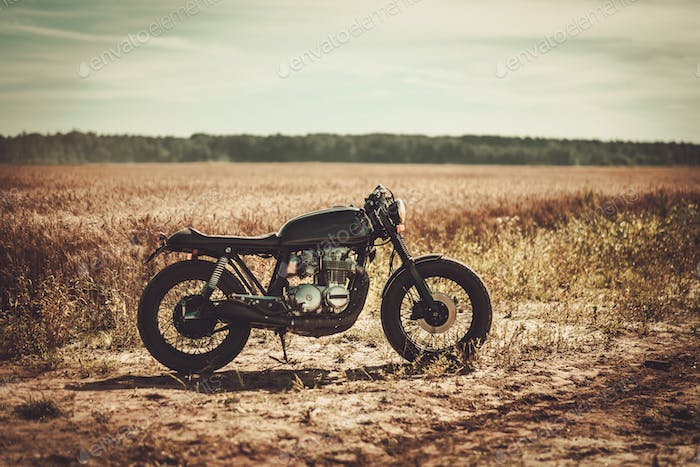 The vintage custom cafe racer in a field