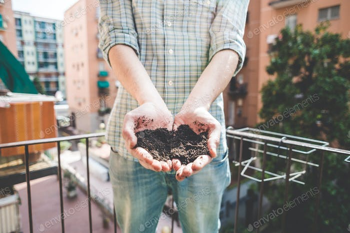 close up of hands holding soil