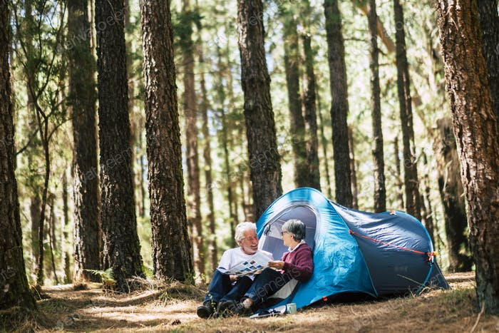 Active people old aged caucasian senior couple travel with camping tent