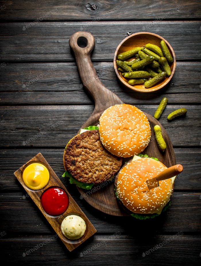 Burgers on a cutting Board with a knife and gherkins in a bowl.