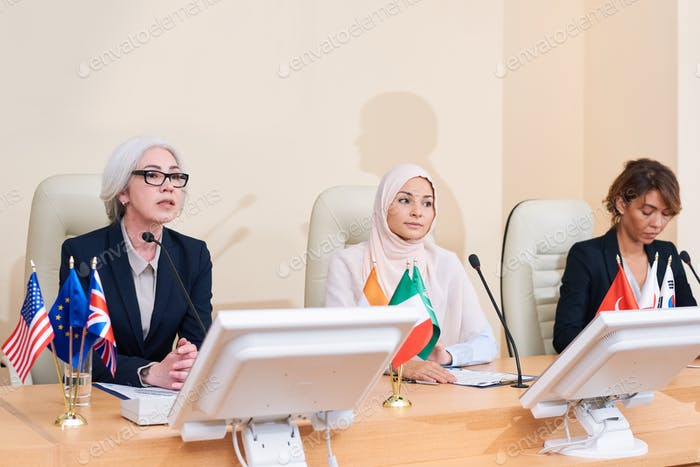 Three intercultural businesswomen in formalwear sitting by table