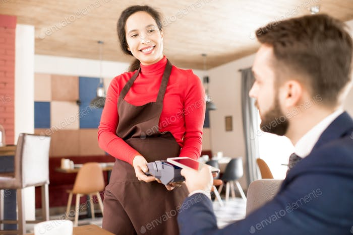 Friendly waitress taking payment from guest
