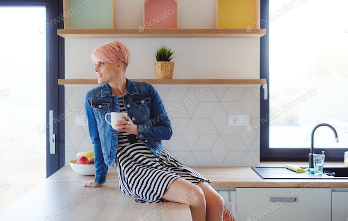 Eine junge attraktive Frau sitzt auf einer Theke in einer Küche zu Hause.