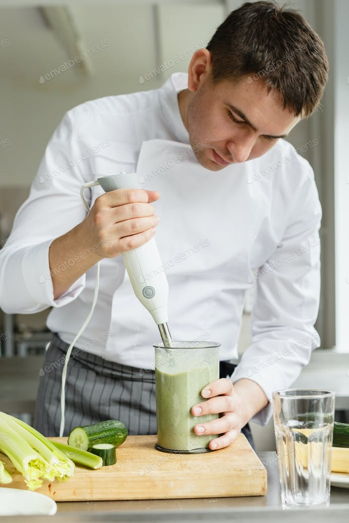 Young male chef making smoothie