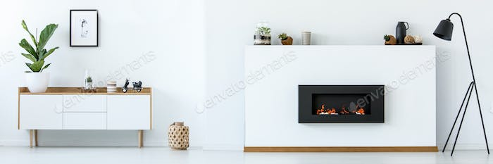 White room interior with fireplace, black metal lamp, cupboard w
