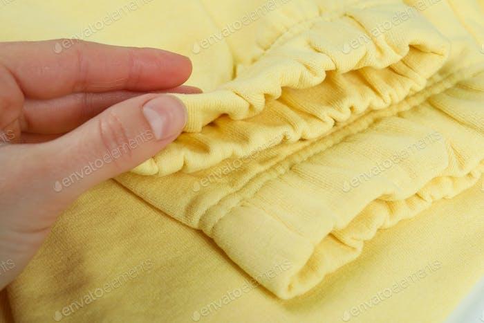 Pantalones de chándal amarillos de mano femenina, de cerca