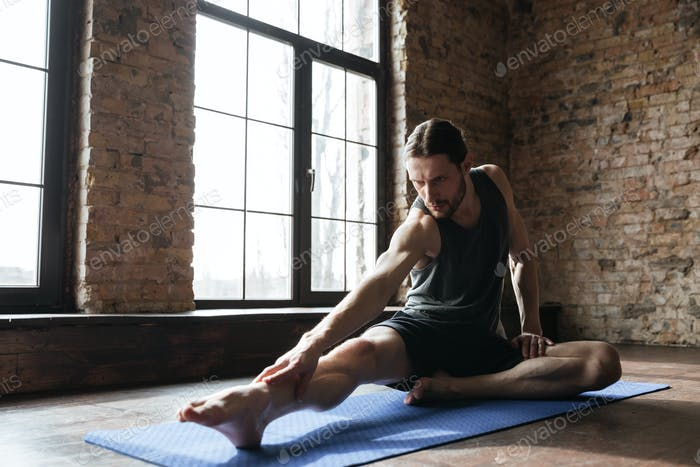 Young concentrated sportsman stretching muscles on the fitness mat