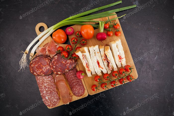 Top view of club sandwiches next to a board with appetizers