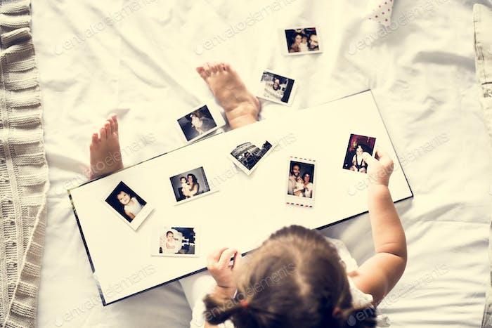Little girl looking her family photo in album