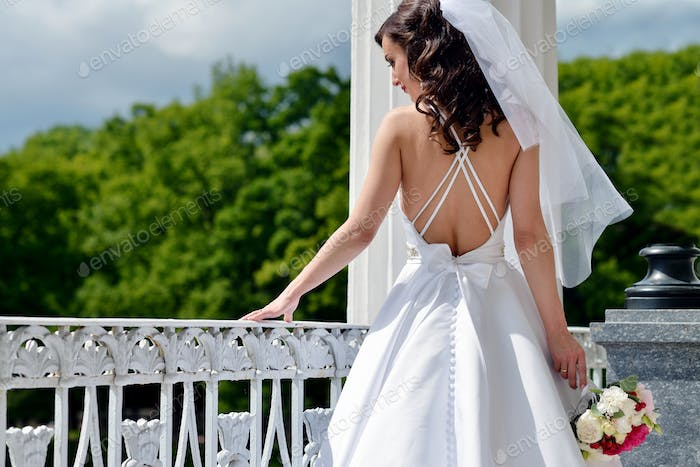 Beauty bride in bridal gown with bouquet and lace veil in the nature