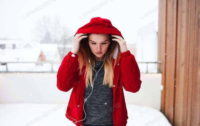 A portrait of young girl or woman with earphones outdoors, listening to music.