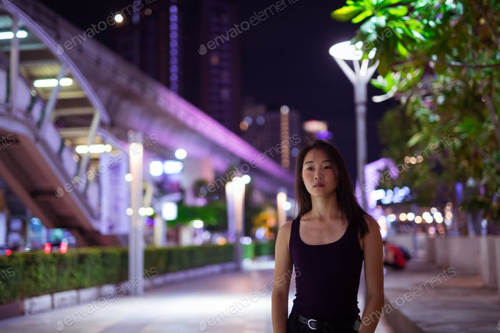 Portrait Of Beautiful Asian Woman Outdoors At Night