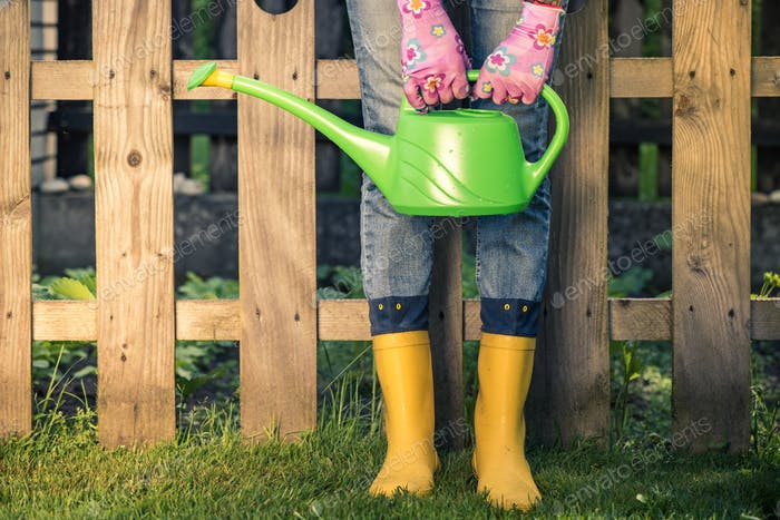 Gardener in yellow wellies and watering can