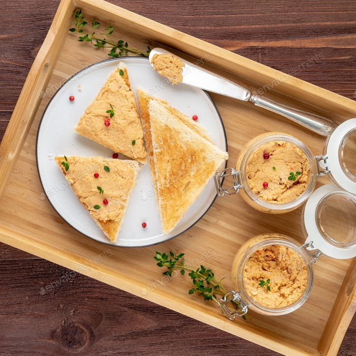 Fresh homemade chicken pate on toasted bread on tray over rustic background, top view