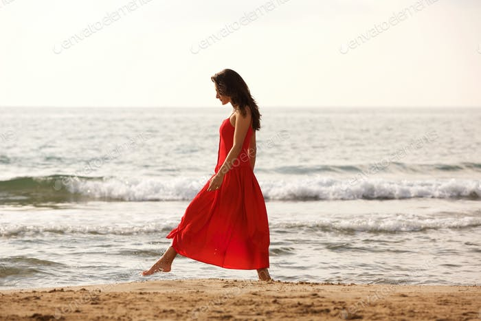 Full length beautiful woman in red dress walking alone on beach