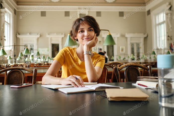 Young attractive smiling girl student happily looking in camera studying in library of university
