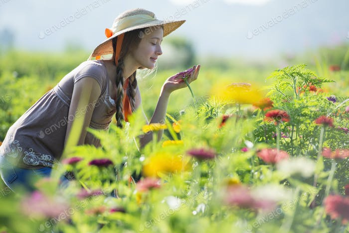 Summer on an organic farm. A young woman in a field of flowers.