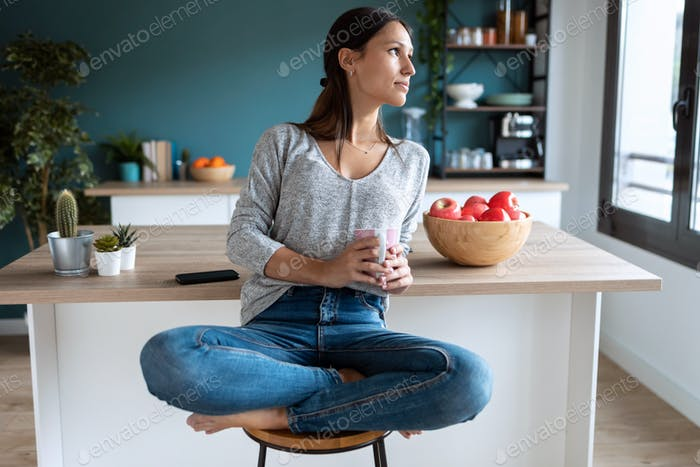 Thoughtful young woman looking to the side sitting on the stool in the kitchen.