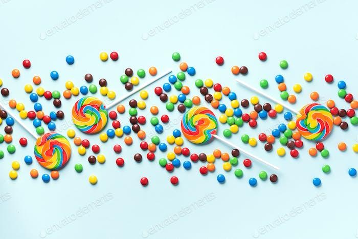 Bunte Lutscher, Regenbogen bunte Süßigkeiten auf blauem Hintergrund. Schokoladen-Süßstücke mit beschichteter Schokolade