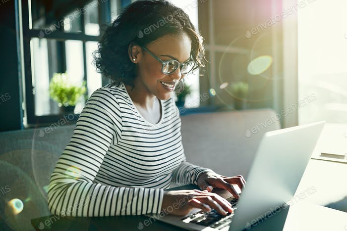Young African woman smiling and working online with a laptop