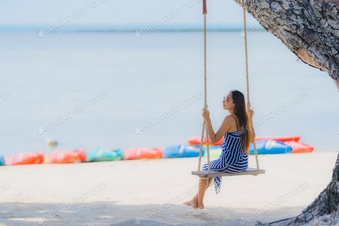 Portrait young asian woman sitting on swing rope and sea around
