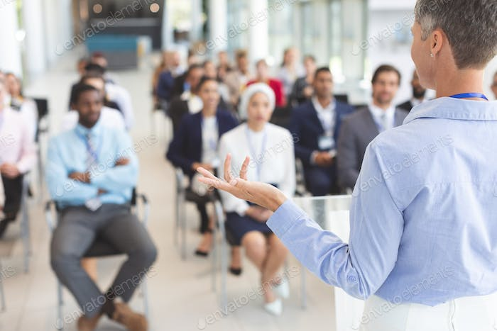 Female speaker speaks to business people in a business seminar in conference