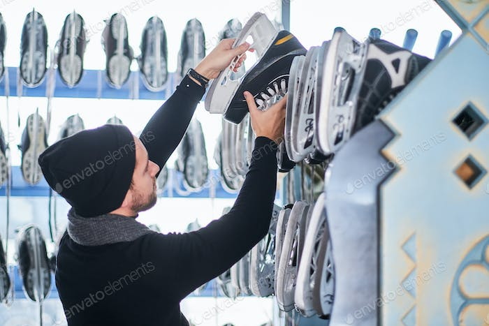 Young guy choosing a pair of skates in a skate hire inside.