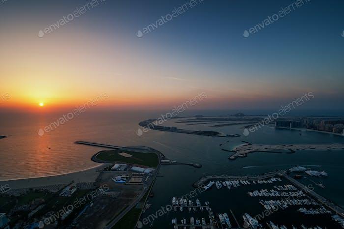Dock with several luxury yachts and extraordinary island. Dubai marina, United Arab Emirates.