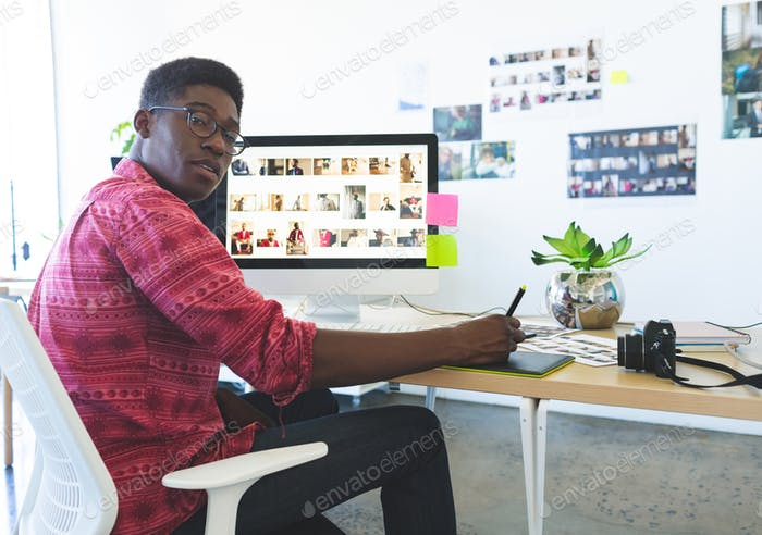 Young graphic designer working on graphic tablet at desk in office