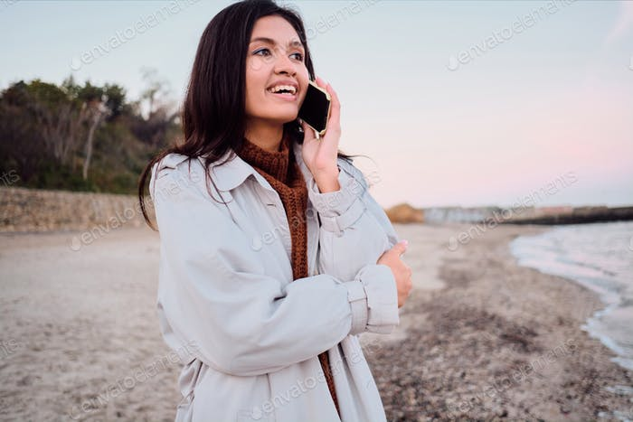Attractive smiling Asian brunette girl happily talking on cellphone walking by the sea