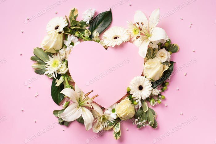 Frame of white flowers, paper heart over pink background. Valentines day, Woman day concept. Spring