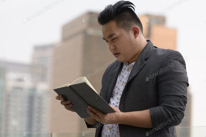 Young overweight Asian businessman reading book in the city