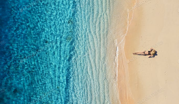 Ein Mädchen, das sich am Strand ausruht. Der Blick aus der Luft. Insel Bali, Indonesien.