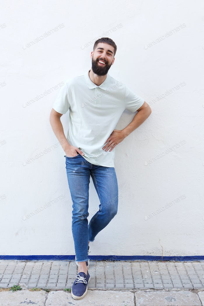 Full length confident man with beard laughing standing by wall