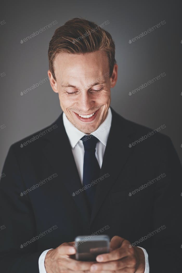 Smiling businessman sending text messages against a gray background