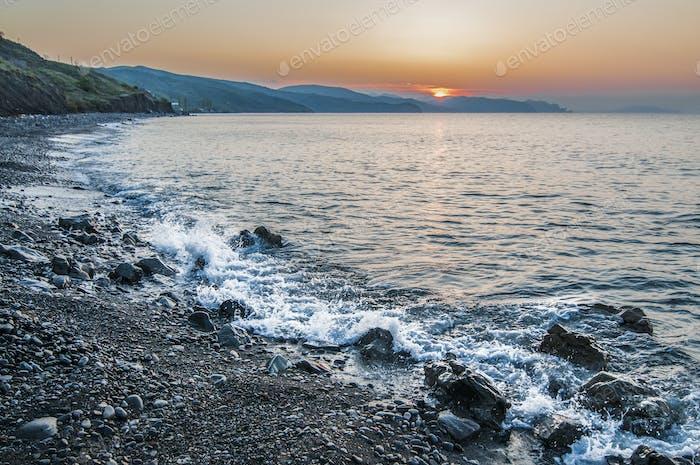 Sunset on the seashore, rocky beach