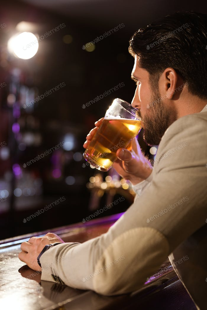 Close up of a man holding glass of beer