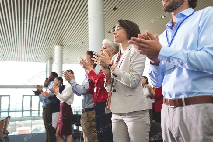 Diverse business people applauding standing at a business seminar in office building