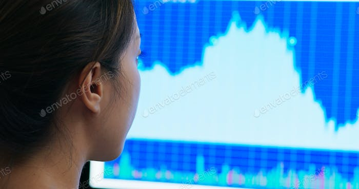 Woman look at the stock market data on computer monitor