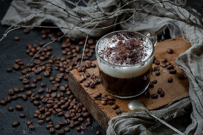 Cappuccino Kaffee mit Milchschaum und Schokolade auf einem Holzbrett