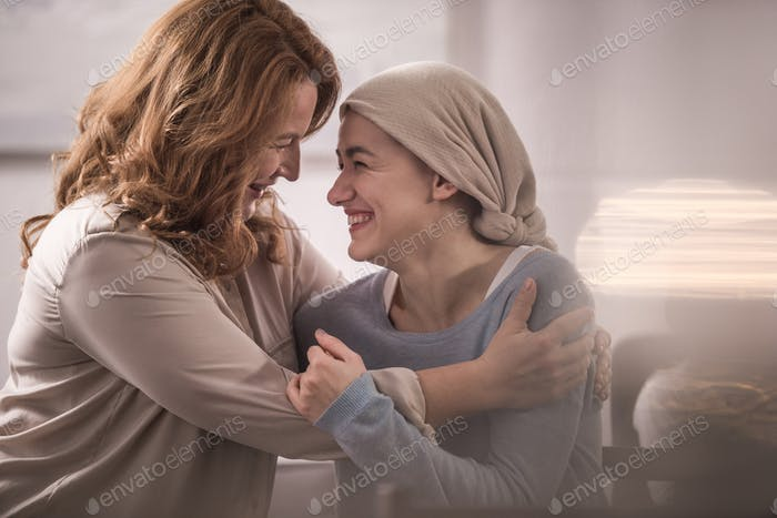 happy mother and sick adult daughter in kerchief hugging and looking at each other