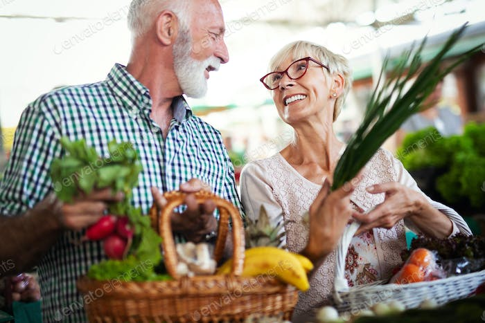 Senior shopping couple with basket on the market. Healthy diet