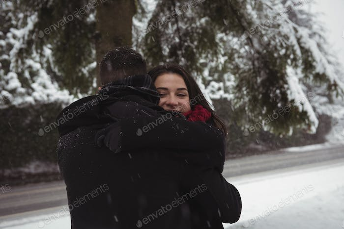 Couple embracing in forest during winter