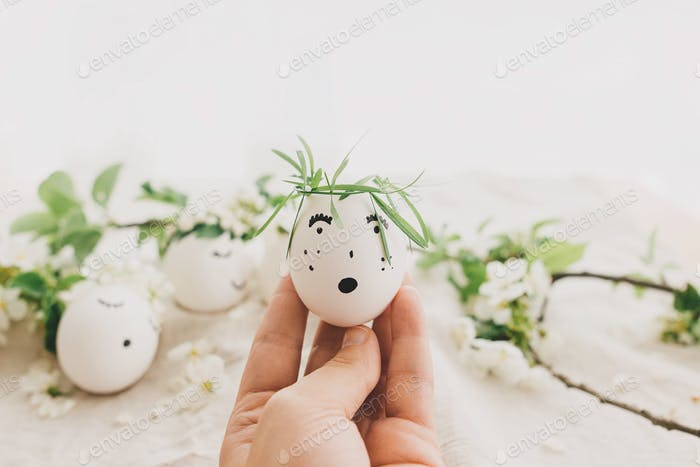 Hand holding easter egg with drawn funny face in floral wreath. Happy Easter and Easter hunt