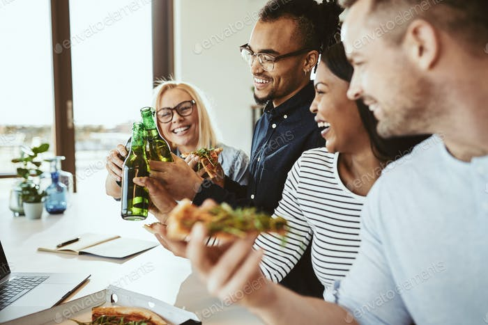 Diverse businesspeople laughing and cheering with beers and eating pizza