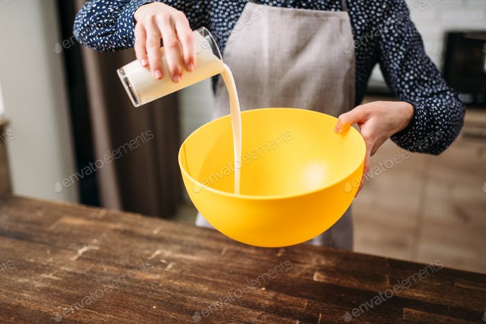Female person adds cream into a bowl, cake cooking