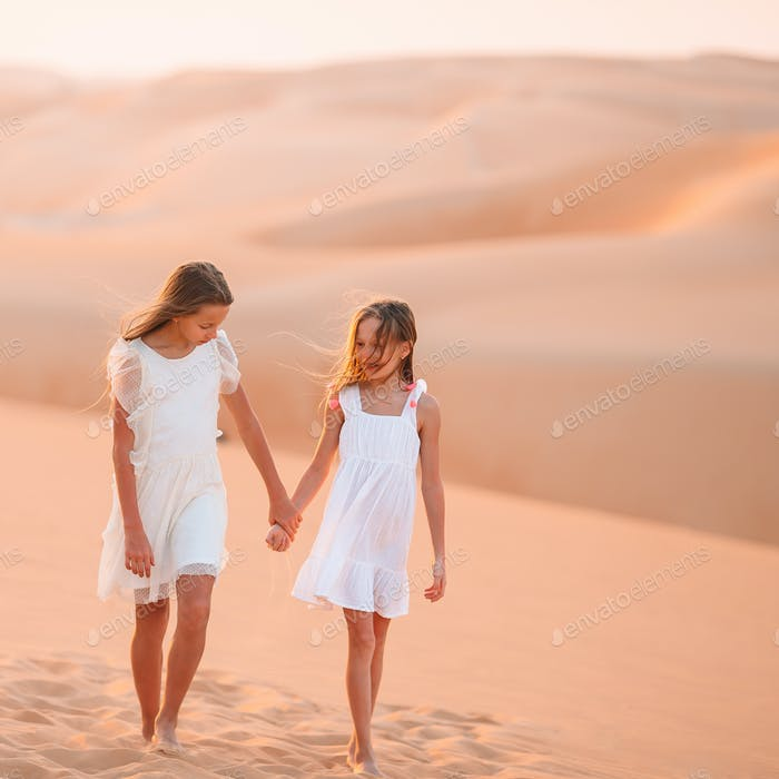 Girls among dunes in big desert in Emirates